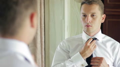 Young handsome man groom in a white shirt standing in front of a mirror and Stock Footage
