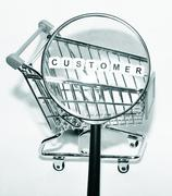 Focus on customer concept with magnifying glass and shopping cart Stock Photos