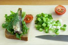 sprats, onion and tomatoes on a cutting board - stock photo