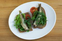 Sprats, bread and tomatoes on a saucer Stock Photos