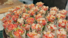 Waiter puts the pieces of fish in portions of vegetable salad on a tray in the Stock Footage