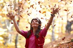 Beautiful girl with falling leaves - stock photo