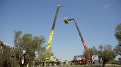Stock Video Footage of Wide establish shot construction machinery,crane lowering workers on platform