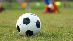 Soccer ball on the grass and training children - stock footage