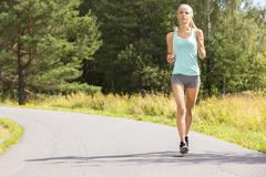 Young woman runs outdoor in the forest - stock photo