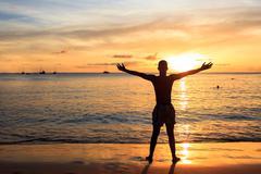 African  men raising arms up  at Sunset in Tarrafal beach in Santiago island  Kuvituskuvat