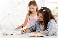 a teenage girl and her younger sister at his desk - stock photo