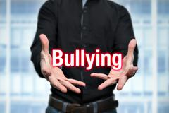 Mobbing, bullying, man holds lettering in the hands Stock Photos