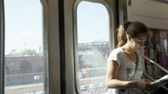 Attractive woman with ponytail leaning against subway doors reading book NYC Stock Footage