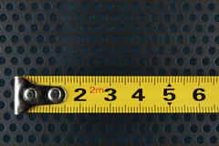 Measuring tape on a background with perforation of round holes Stock Photos