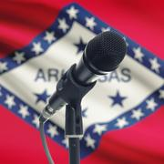Microphone on stand with US state flag on background - Arkansas - stock photo