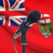 Microphone on stand with Canadian province flag on background - Manitoba Stock Photos