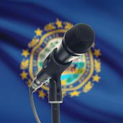 Microphone on stand with US state flag on background - New Hampshire - stock photo