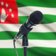 Microphone on stand with national flag on background - Abkhazia - stock photo