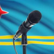 Microphone on stand with national flag on background - Aruba - stock photo