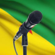 Microphone on stand with national flag on background - French Guiana - stock photo