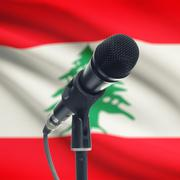 Microphone on stand with national flag on background - Lebanon - stock photo