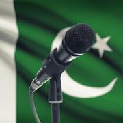 Microphone on stand with national flag on background - Pakistan - stock photo