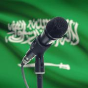 Microphone on stand with national flag on background - Saudi Arabia - stock photo