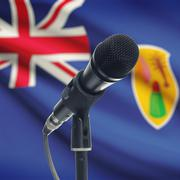 Microphone on stand with national flag on background - Turks and Caicos Islan - stock photo