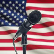 Microphone on stand with national flag on background - United States Stock Photos