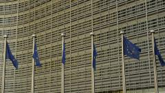 European Commission buildings and European Union flags at sunset Stock Footage