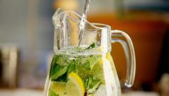 Lemonade with Lemon and Lime pouring in slow motion Stock Footage