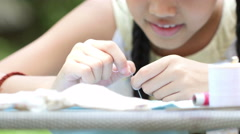 Asian girl practices to sewing a dress for her doll with needles and thread Stock Footage