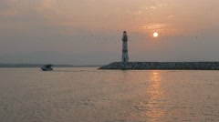 Boats passing lighthouse with rising sun at background. 4K Stock Footage