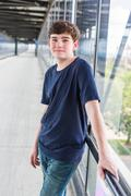 Teenage boy at the lightrail station in urban area - stock photo