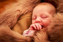 closeup portrait of newborn baby sleeping face and sucking finger - stock photo