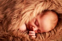closeup portrait of newborn baby sleeping face with hand under cheek - stock photo