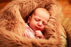 newborn baby sleeping with small hand near cheek - stock photo