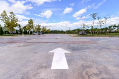 White arrow on car park with cars background. Stock Photos