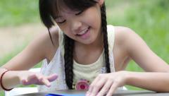 Little Asian girl makes boat from colored paper Stock Footage