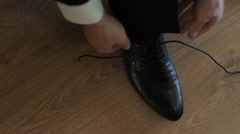 Groom puts on shoes and tying shoelaces Stock Footage