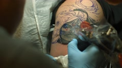 Over the Shoulder Shot of Tattoo Artist Working on Sugar Skull Tattoo Stock Footage
