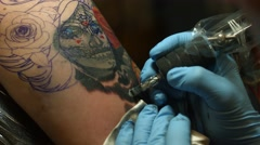 Tattoo Artist Adding Color to the Sugar Skull Stock Footage