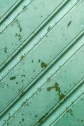 Old green wooden wall with peeling paint and drops of water, diagonal pattern - stock photo