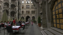 People walking out from a restaurant in the courtyard of New Town Hall, Munich - stock footage