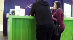 People asking telus sales clerk about cellphone plan - stock footage