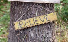 A wooden plaque with the word - believe - stock photo