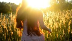 Girl in a pink dress and long dark hair running across the field Stock Footage