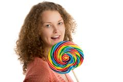 Girl with giant lollypop licks her lips - stock photo