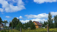 Rural house with uncultivated field with wild flowers under blue sky, time lapse Stock Footage