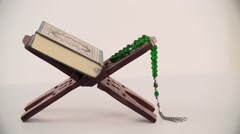 Holy Quran and prayer beads on stand. Stock Footage