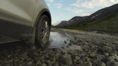 Pov, car driving across mountain river, tire riding on gravel road Stock Footage
