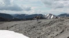 Mountaineer walking on mountain peak near snowfield at summer season - stock footage