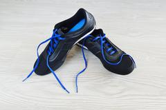 Sneakers with blue laces are on  floor - stock photo