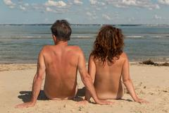 Stock Photo of Naked couple sitting on the beach.